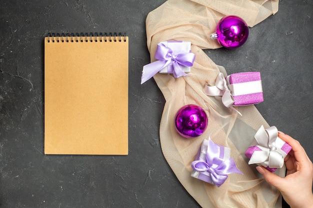 Visão aérea de acessórios de decoração de presentes coloridos para o ano novo em toalha de cor nude e caderno em fundo preto