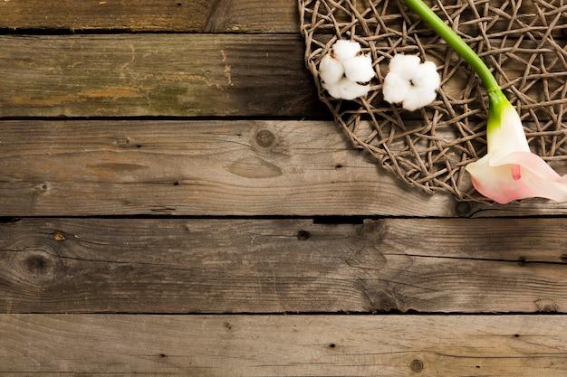 Visão aérea de algodão com flores na mesa de madeira