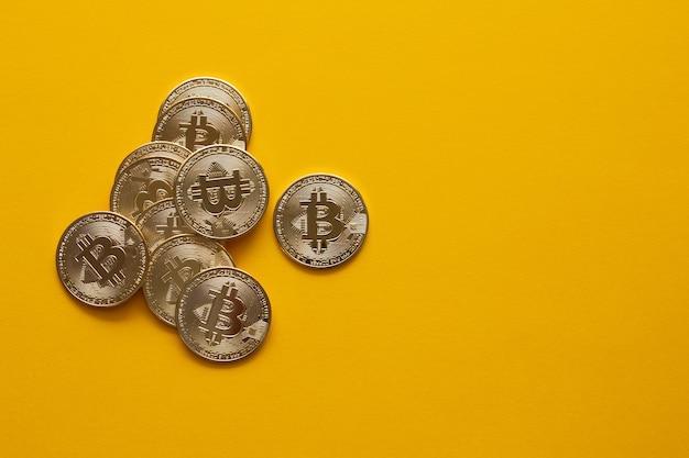 Visão aérea de alguns bitcoins dourados em um fundo amarelo e espaço de cópia