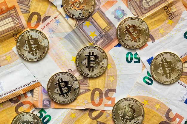 Visão aérea de alguns bitcoins em notas de cinquenta euros