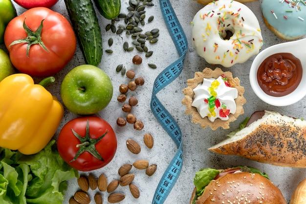 Visão aérea de alimentos saudáveis e insalubres com fita métrica sobre fundo