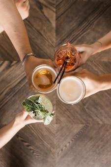 Visão aérea, de, amigo, mãos, brindar, bebidas