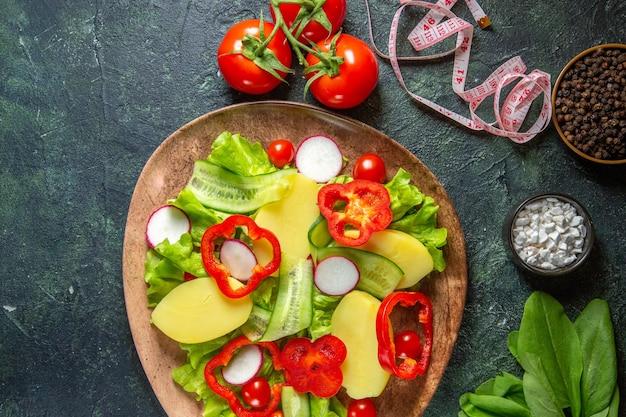 Visão aérea de batatas cortadas descascadas frescas com rabanetes de pimenta vermelha, tomates verdes em um prato marrom e mede especiarias em uma superfície de cores pretas e verdes