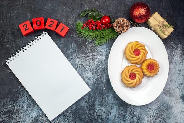Visão aérea de biscoitos deliciosos em um prato branco e caderno de presente de inscrição de decorações de ano novo na superfície escura