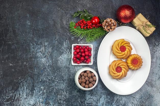 Visão aérea de biscoitos deliciosos em um prato branco e cornel de presente de decorações de ano novo em uma pequena panela de chocolate na superfície escura
