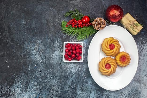 Visão aérea de biscoitos deliciosos em um prato branco e cornel de presentes de decorações de ano novo em uma panela pequena na superfície escura