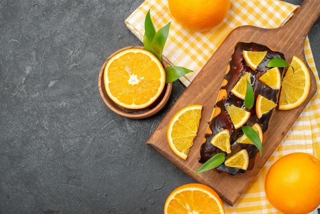 Visão aérea de bolos moles inteiros e laranjas cortadas com folhas na mesa escura