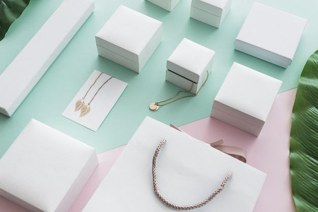Visão aérea de caixas brancas com jóias de ouro sobre fundo de papel colorido