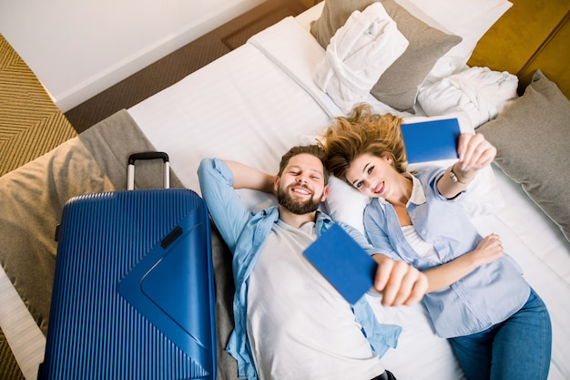 Visão aérea de casal de turistas, mulher bonita e homem bonito com roupa casual, deitado na cama no quarto de hotel, mostrando seus passaportes. viagem, hotel, conceito de reserva