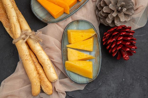 Visão aérea de deliciosas fatias de queijo e cones de coníferas em uma toalha em um fundo preto