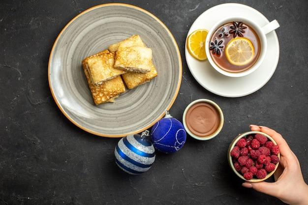 Visão aérea de deliciosas panquecas frescas em um prato branco e uma xícara de chá preto com acessórios de decoração de framboesa de chocolate em fundo escuro