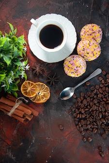 Visão aérea de deliciosos biscoitos de açúcar e uma xícara de café em um vaso de flores limões secos e grãos de fatias de canela em um fundo de cores misturadas.