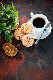Visão aérea de deliciosos biscoitos de açúcar e uma xícara de café em um vaso de flores secas de fatias de limão em um fundo escuro de cores misturadas