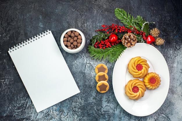 Visão aérea de deliciosos biscoitos em um prato branco, chapéu de papai noel e chocolate em uma tigela ao lado do caderno na superfície escura