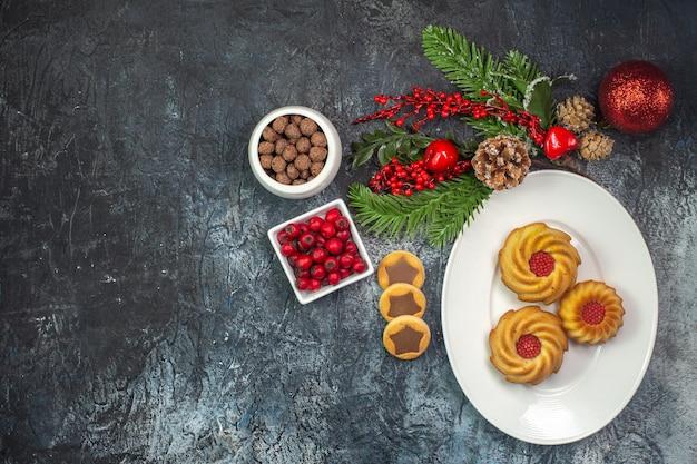 Visão aérea de deliciosos biscoitos em um prato branco, chapéu de papai noel e cornel de chocolate em uma tigela, decorações na superfície escura