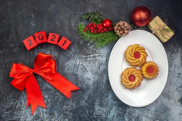 Visão aérea de deliciosos biscoitos em um prato branco e a inscrição de decorações de ano novo ao lado do presente na superfície escura