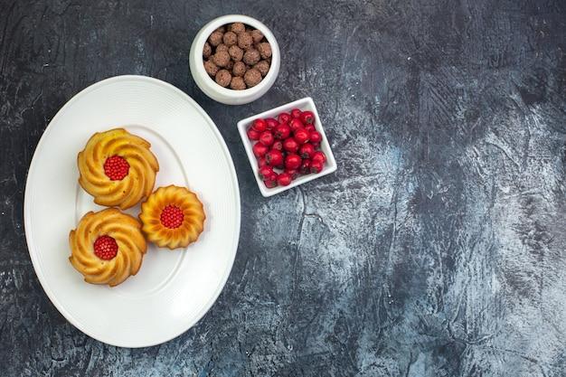 Visão aérea de deliciosos biscoitos em um prato branco e chocolate cornel na superfície escura das tigelas