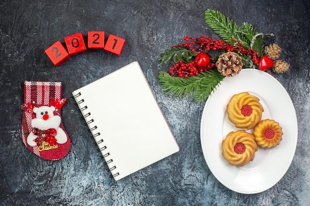 Visão aérea de deliciosos biscoitos em um prato branco e decorações. chapéu de papai noel com números da meia de ano novo ao lado do caderno na superfície escura