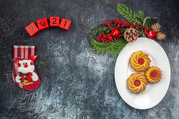 Visão aérea de deliciosos biscoitos em um prato branco e decorações chapéu de papai noel números meias de ano novo na superfície escura