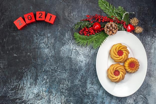 Visão aérea de deliciosos biscoitos em um prato branco e decorações de ano novo, chapéu de papai noel ao lado de números na superfície escura