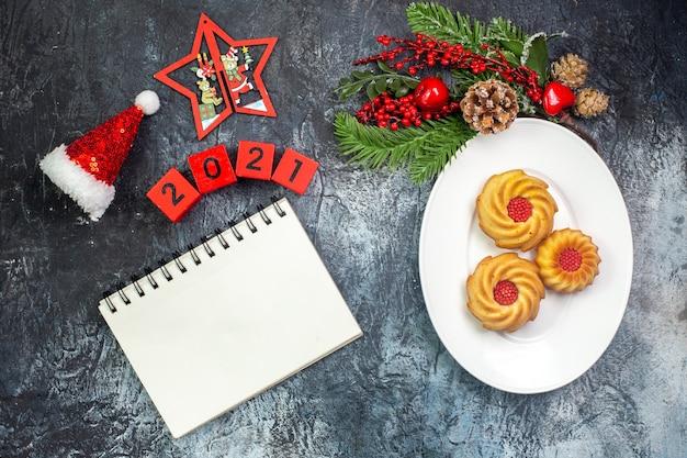 Visão aérea de deliciosos biscoitos em um prato branco e decorações de ano novo, chapéu de papai noel ao lado dos números do caderno na superfície escura