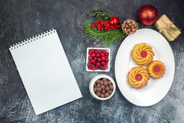 Visão aérea de deliciosos biscoitos em um prato branco e decorações de ano novo presente em uma panela pequena e um caderno na superfície escura