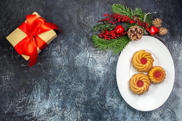 Visão aérea de deliciosos biscoitos em um prato branco e um presente de decoração de ano novo com fita vermelha na superfície escura