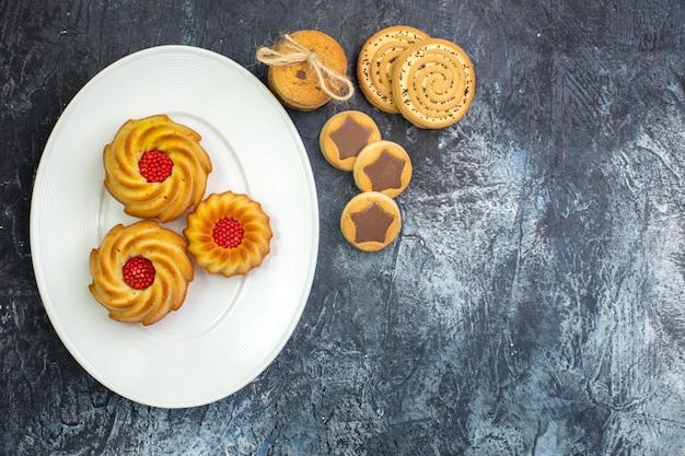 Visão aérea de deliciosos biscoitos em um prato branco e vários biscoitos e garfo na superfície escura