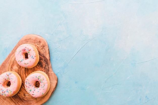 Visão aérea de deliciosos donuts na tábua de madeira