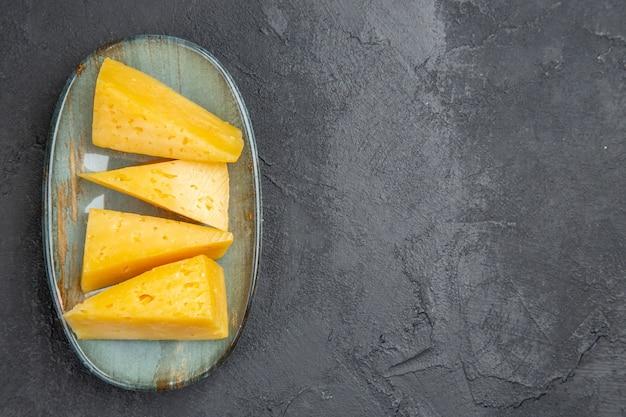 Visão aérea de deliciosos queijos fatiados em amarelo em um prato azul no lado direito sobre fundo preto