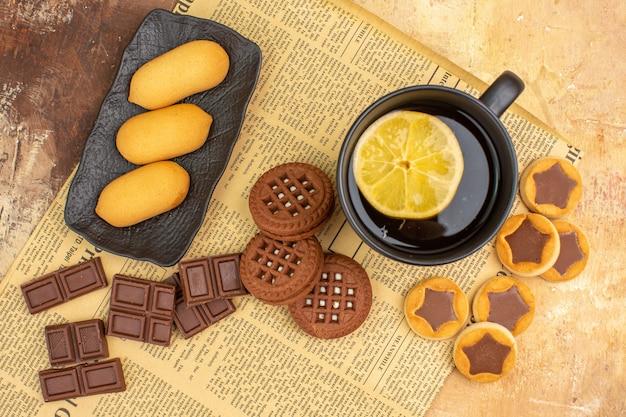 Visão aérea de diferentes biscoitos e chá em uma xícara preta na mesa de cores diferentes