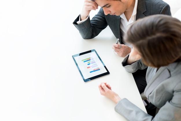 Visão aérea de dois colegas de trabalho, um homem e uma mulher, analisando um gráfico estatístico de negócios em um computador tablet enquanto se sentam lado a lado na mesa.
