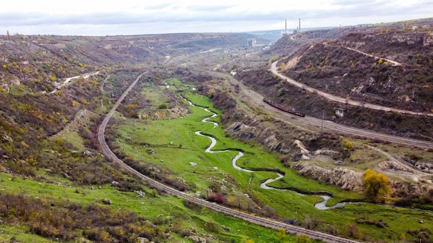 Visão aérea de drones da natureza na moldávia, fluxo do riacho que flui para a ravina, encostas com vegetação esparsa e rochas, trem em movimento, céu nublado