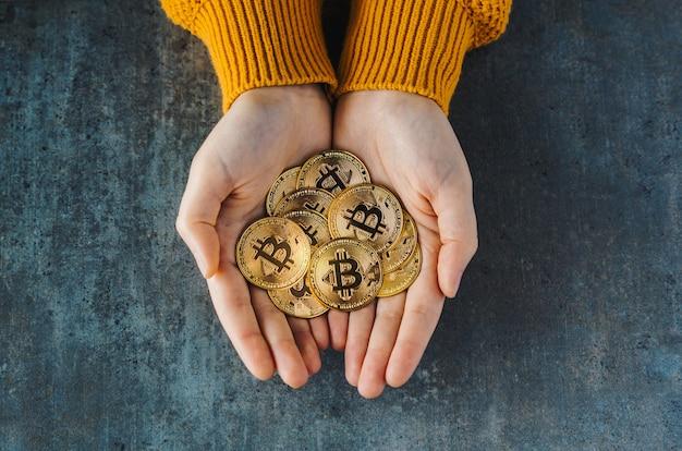 Visão aérea de duas mãos cheias de bitcoins em um plano de fundo texturizado