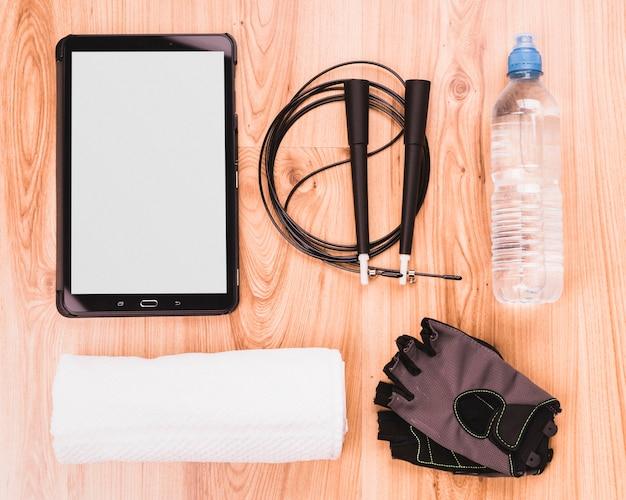 Visão aérea de equipamentos de fitness e tablet digital no piso de madeira