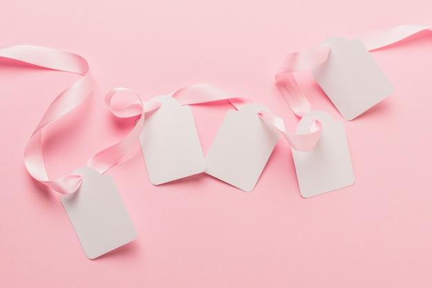 Visão aérea de etiquetas em branco e fita rosa contra o pano de fundo rosa claro