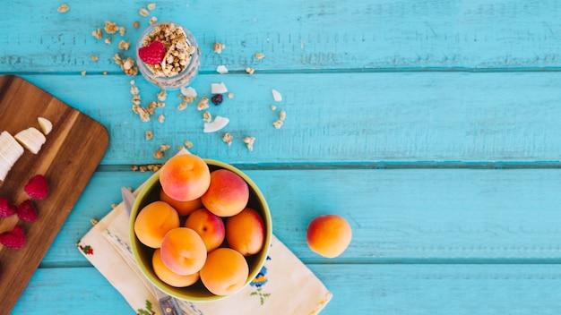 Visão aérea de fatias de banana; morangos; pêssego e aveia no topo de mesa de madeira azul