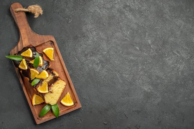 Visão aérea de fatias de bolo macio recém-assado na tábua de madeira na mesa escura