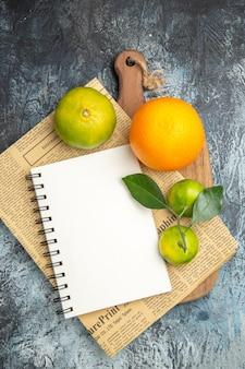 Visão aérea de frutas cítricas frescas com folhas de jornal na tábua de madeira cortadas ao meio na mesa cinza