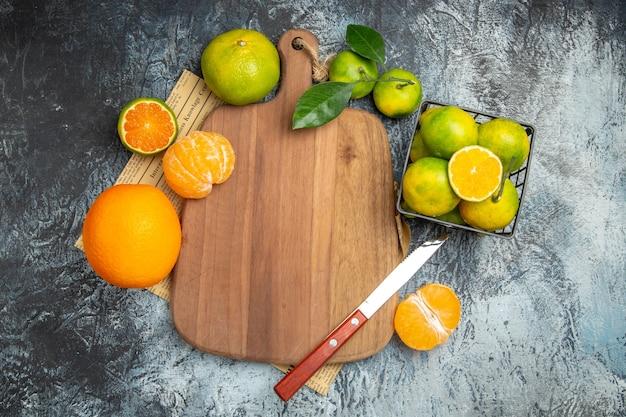 Visão aérea de frutas cítricas frescas com folhas na tábua de madeira cortadas ao meio e faca no jornal sobre fundo cinza