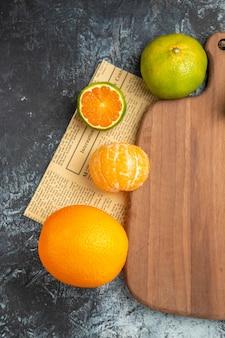 Visão aérea de frutas cítricas frescas com folhas na tábua de madeira cortadas ao meio na mesa cinza do jornal