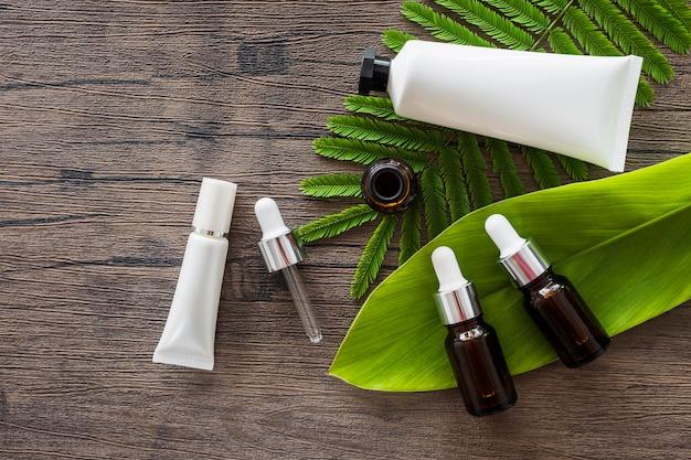 Visão aérea de garrafas de óleo essencial e tubo branco cosmético em folhas verdes sobre a mesa de madeira