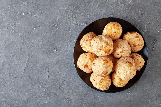 Visão aérea de gougeres, bolinhos de queijo em uma placa preta. pãezinhos de queijo francês tradicional em uma mesa de concreto, vista de cima, flatlay, close-up, espaço de cópia