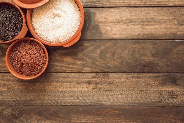 Visão aérea de grãos de arroz na tigela na mesa de madeira