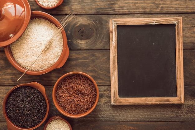 Visão aérea de grãos de arroz orgânico na tigela com lousa em branco