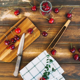 Visão aérea de guardanapo com faca e cerejas vermelhas frescas na tábua de madeira
