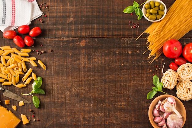 Visão aérea de ingredientes para fazer massa italiana em fundo de madeira