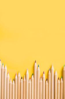 Visão aérea de lápis coloridos em pano de fundo amarelo