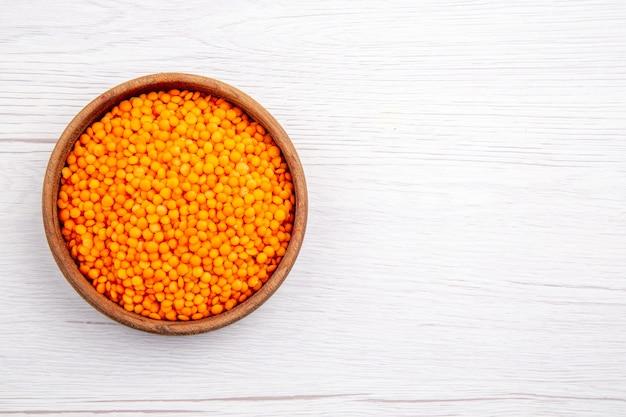 Visão aérea de lentilhas amarelas em uma tigela marrom no lado direito em fundo branco