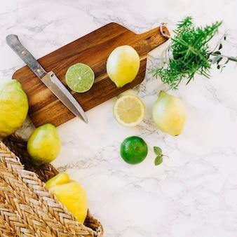 Visão aérea de limão e faca na tábua de madeira